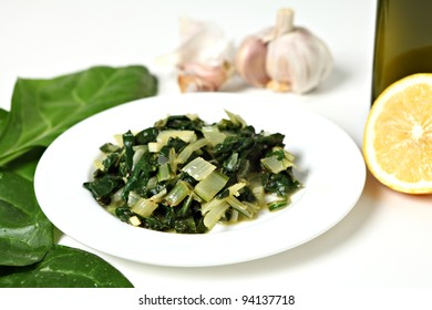 A side dish of swiss chard cooked in olive oil with garlic and chili flakes and then tossed in lemon juice, with raw ingredients