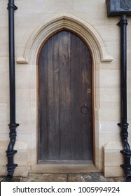 A side door to a church with metal drainpipes running down either side of it.