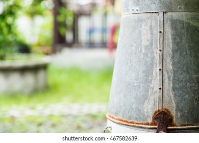 up side down rusted zinc water bucket in garden, with copy space