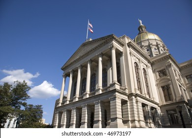 Side entrance to a state capitol building with blue sky and clouds in the background. Horizontal shot.