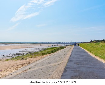 At the side of the Estuary, on the top of a stone lined embankment people walk along a path towards the sea.