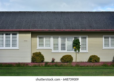 Side exterior wall of wooden house with pane windows in wooden frames and weatherboard cladding and corrugated roof.