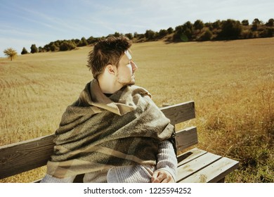 Side face of a sitting young man with the eyes closed enjoying in calm the morning autumn sun in a yellow field