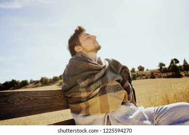Side face of a young man with the eyes closed enjoying in calm the morning autumn sun in a yellow field with the backlight from the blue sky