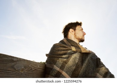 Side face of a young man with the eyes closed enjoying in calm the morning autumn sun with the backlight from the blue sky
