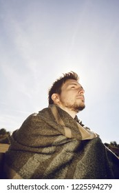 Side face of a young man with a warm scarf enjoying in calm the morning autumn sun with the backlight from the blue sky
