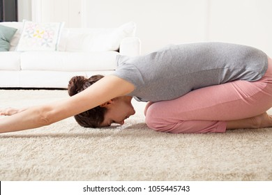 Side figure view of beautiful woman stretching body in home interior living room doing yoga, eyes closed, healthy well being indoors. Mature female practicing yoga serene, wellness leisure lifestyle.