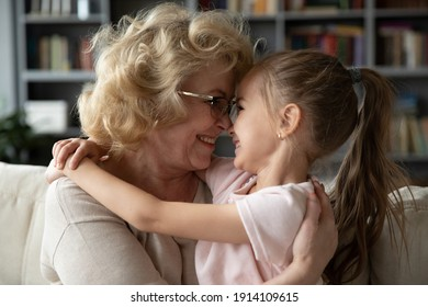 Side head shot view caring affectionate elderly retired 60s grandmother in eyeglasses cuddling smiling adorable little preschool kid girl, showing love and devotion to granddaughter in living room.