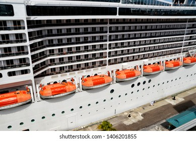 side of huge Cruise liner with lifeboats docked in Nassau, Bahamas islands.