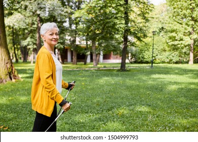 Side image of energetic sporty female pensioner in stylish clothes doing physical exercises using Nordic walking sticks, feeling full of energy, being in good mood. Aged people and active lifestyle
