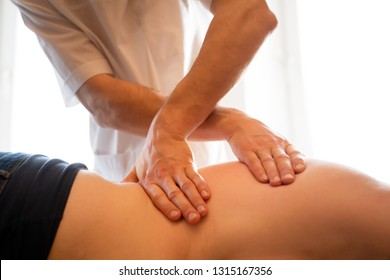 Side image of hands of man massaging young woman.