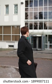 Side image of short hair senior woman posing outside in black coat. Office building on background. Copy space. Horizontal photo of woman looking back, unrecognizable. Lifestyle, work, travel concept