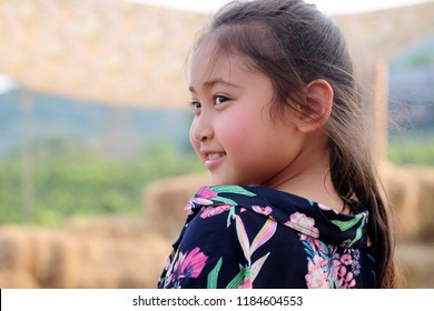 Side of little Asian girl with bright smile and healthy. Isolated on natural background.