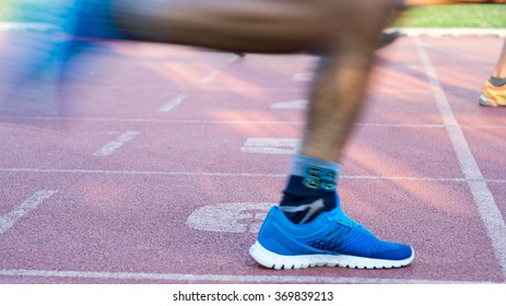 Side low angle view of unidentifiable runners leaving a racing track finishing line in fast motion
