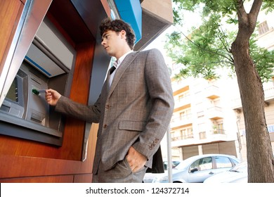 Side low view of an elegant businessman withdrawing money from a wood decorated bank cash point, outdoors.
