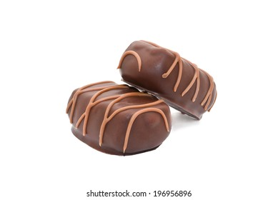 Side macro shot of two chocolate candies isolated on white background.