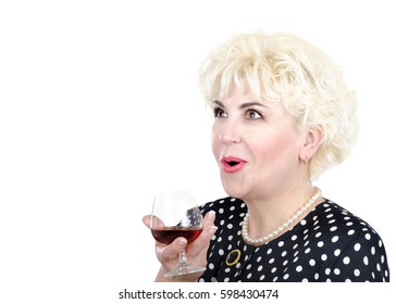 Side medium close up studio shot of admiration stunning adult lady with open mouth.  Blonde hair woman holds glass of brandy dresses polka dot suit pearl necklace and bracelet on white background