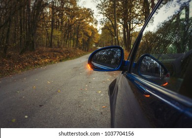 Side mirror turn signal. Turn indicator on the mirror (left) and blue car on the road in autumn forest.  Car stands on the edge of the road in forest.