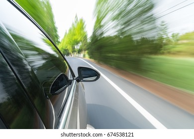 side mirror view of car driving with trees on both sides of the road, fast motion blur