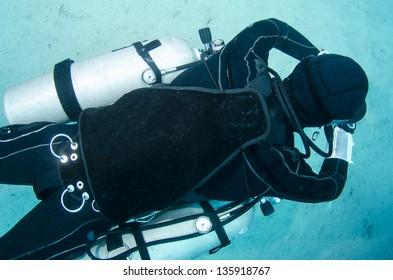 side mount scuba diver swims in the ocean