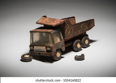 Side of an old, dirty and very rusty tin metal model toy of a dump truck in blue and grey color isolated on white background. Wheels have fallen off. concept of broken toys.