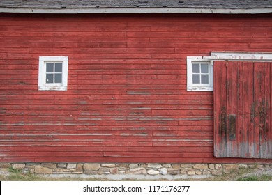Side of an old red barn with white framed square windows and sliding door.
