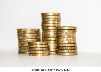 Side on view of four stacks and column of gold one dollar and two dollar coins isolated on white.