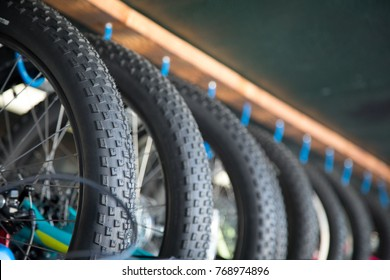 Side perspective close up on a row of black rubber mountain bike tires hanging on a rack at a bicycle shop