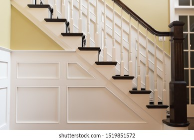 Side picture of staircase with white modern wainscoting and black square wooden post and white balusters and painted yellow wall