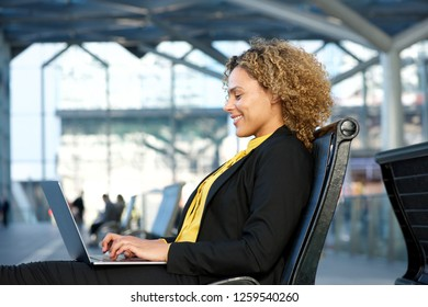 Side portrait of african american business woman working on laptop