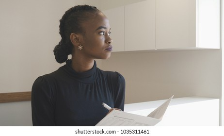 Side portrait of the african woman with natural make-up at the reception. Charming brunette is thoughtfully looking aside while holding the documents.