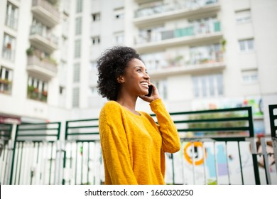 Side portrait attractive young black woman talking with cellphone in city