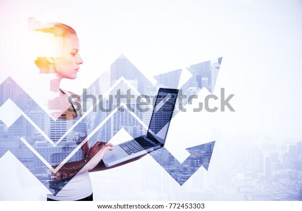 Retrato lateral de una atractiva joven mujer usando un portátil sobre fondo abstracto de ciudad luz con flechas. Tecnología y concepto de éxito. Doble exposición