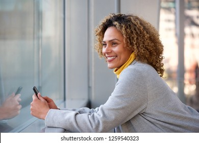 Side portrait of beautiful african american woman smiling with mobile phone