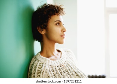 Side portrait of beautiful african american woman leaning against wall and thinking