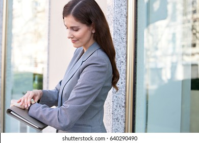Side portrait of beautiful mature business woman carrying folder and looking at her wrist watch in financial city exterior, smiling. Rush hour, time keeping professional wearing suit, sunny outdoors.