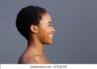 Side portrait of beautiful smiling black female model against gray background