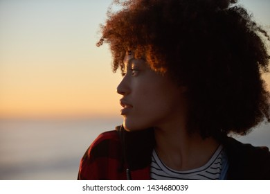 Side portrait of beautiful woman with afro looking at the ocean