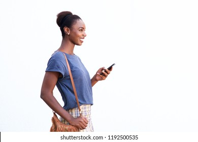 Side portrait of beautiful young african american woman smiling against white isolated background