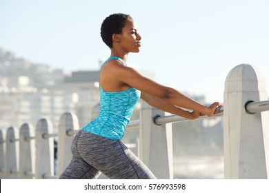 Side portrait of beautiful young black sports woman leaning on railing outdoors