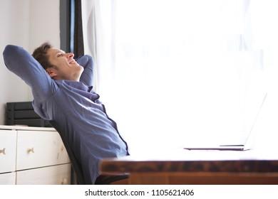Side portrait of business casual man on break leaning back from desk