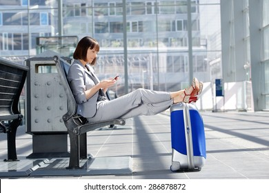 Side portrait of a business woman sitting with bag and mobile phone at airport
