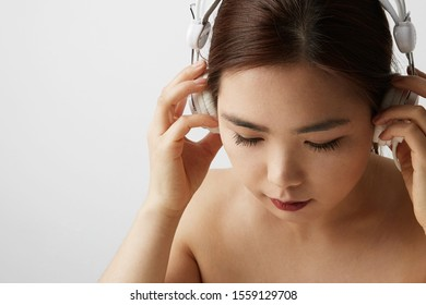 Side portrait of Chinese woman posing on the white background with big earphones. Isolated.