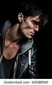 side portrait of a cool man in leather jacket on black background