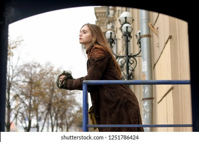 Side portrait of a girl with long brown hair who stands on the balcony. She is dressed in the style of boho: brown cloak, green sweater.