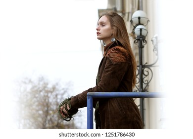 Side portrait of a girl with long brown hair against the background of historic buildings. She is dressed in the style of boho: brown cloak, green sweater.