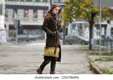 Side portrait of a girl who goes on the sidewalk. She is dressed in a boho style: brown coat, yellow bag, green sweater, shorts and torn stockings