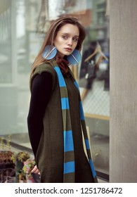 Side portrait of a girl who is standing at the window of a vintage clothing store. She is dressed in a boho style: a green jumpsuit and a long blue scarf.