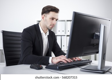 Side portrait of handsome young businessman in suit using computer in modern office