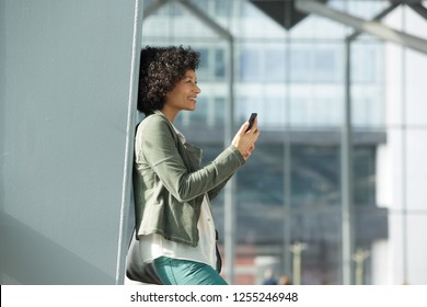 Side portrait of happy african american woman with mobile phone